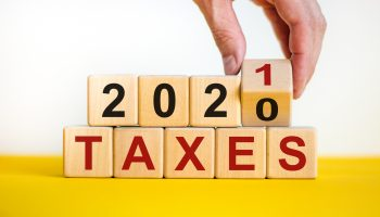 Business concept of planning 2021. Male hand flips wooden cube and change the inscription 'Taxes 2020' to 'Taxes 2021'. Beautiful yellow table, white background, copy space.